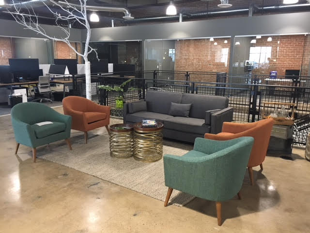 A photo of the lobby area at STC's newly renovated warehouse office at 411 S. 1st Street, in downtown Phoenix, Arizona. The lobby area contains several chairs, a sofa, and a coffee table.